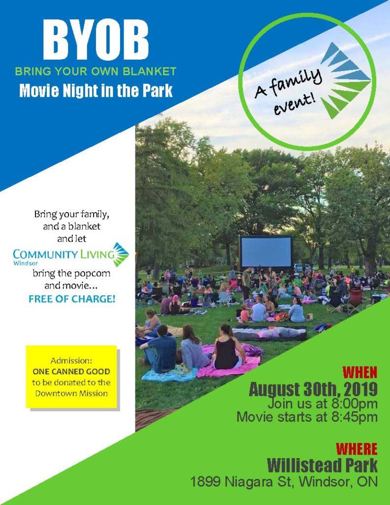 people in park facing movie screen